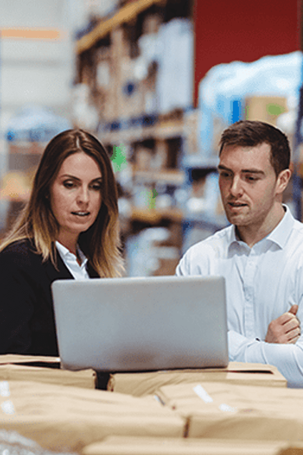 2 people looking at a laptop in a warehouse