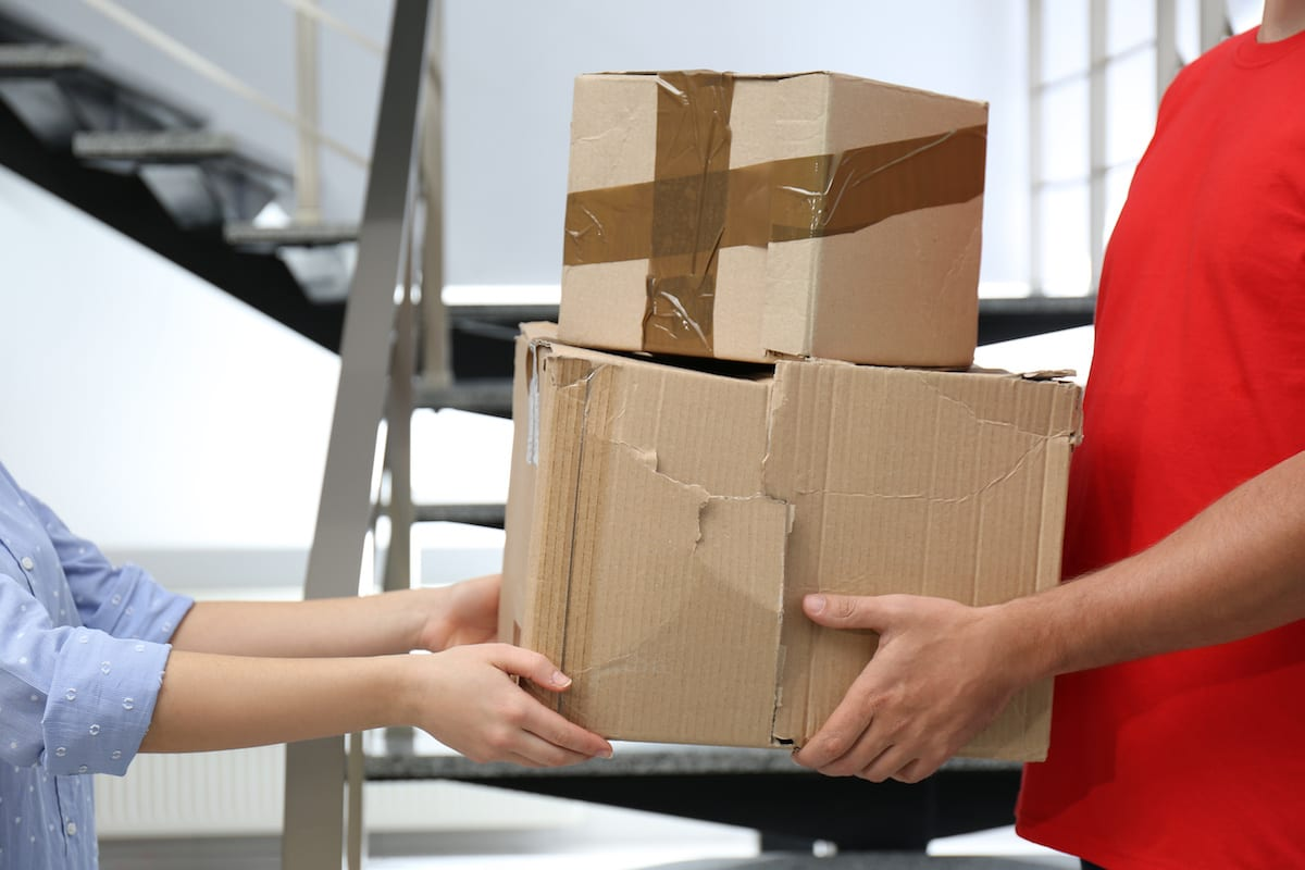 Courier giving damaged cardboard boxes to client indoors, closeup. Poor quality delivery service
