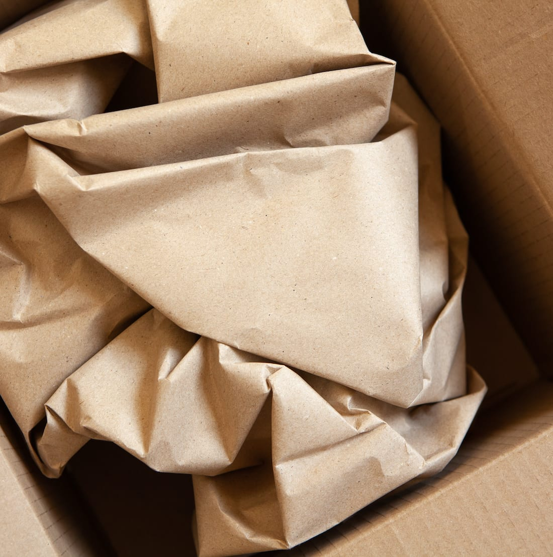 Crumpled wrapping craft brown paper in open after delivery paperboard box. Horizontal. Delivery, ecology, plastic free, resource overrun concept. Flat lay, top view, close-up.